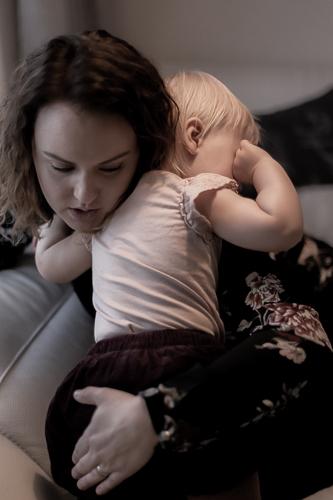 Äiti halaa pientä lasta.