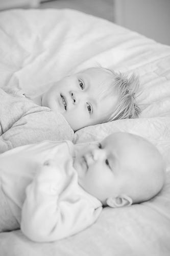 Poika ja vauva sangyllä vierekkäin ja poika katsoo suoraan kameraan.