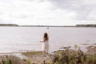 Pieni tyttö heittää kiven järveen.