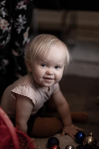 Pieni lapsi istuu lattialla ja nauraa kameralle.