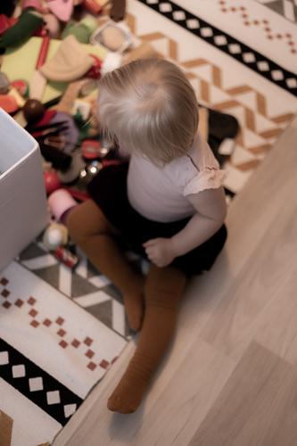 Lapsi istuu lattialla ja leikkii.