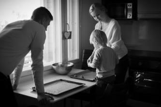 Perhe leipoo yhdessä, mustavalkoinen kuva.