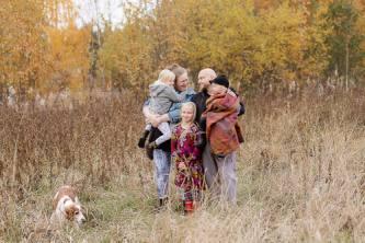 Perhe ja perheen koira pellolla.