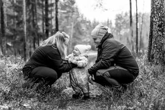 Lapsi äidin ja isän kanssa metsassä.
