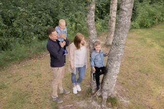 Äiti, isä ja kaksi lasta puun juurella.