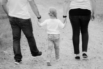 Perhe kävelee pois pitäen toisiaan kädestä kiinni.