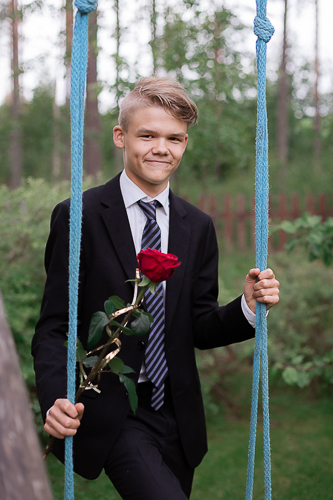 Rippikuvassa poika ruusun kanssa keinussa.