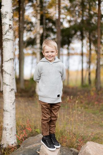 Poika seisoo kivellä ja nauraa.