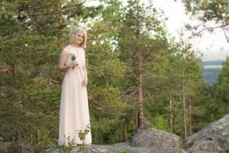 Rippikuvassa tyttö seisoo korkealla kivellä Vuokatinvaaran päällä.