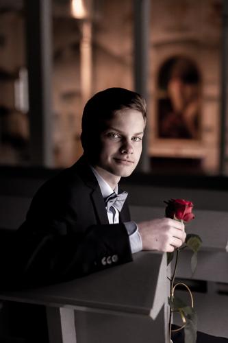Rippikuvassa poika istuu kirkossa punainen ruusu kädessä.