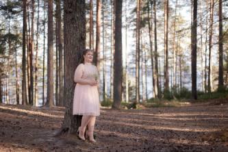 Rippikuvassa tyttö nojaa metsässä isoon mäntyyn.