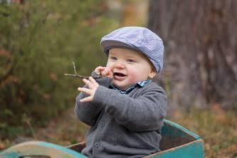 Yksivuotias ihana istuu puun juurella laatikossa puutikku suussa.