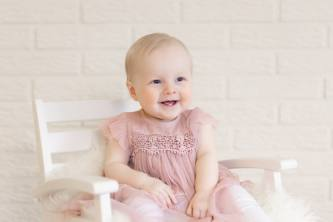 Yksivuotias tyttö istuu keinutuolissa ja nauraa.