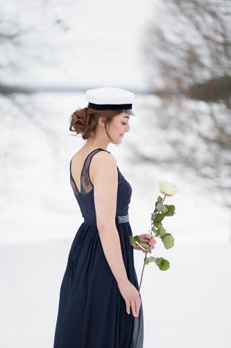 Ylioppilas valkoisen ruusun kanssa lumisessa maisemassa.