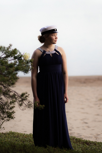 Ylioppilas tyttö seisoo rannalla ja katsoo kaukaisuuteen.