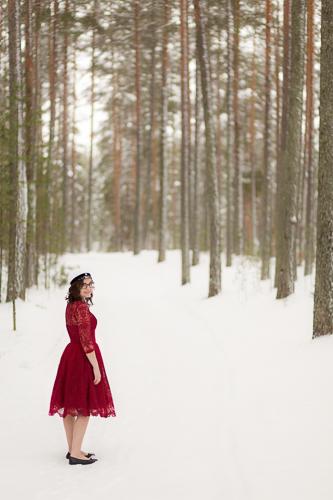 Ylioppilas talvisessa metsässä punaisessa mekossa.
